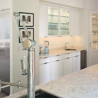 Exempel på ett stort klassiskt vit vitt kök, med en integrerad diskho, luckor med infälld panel, vita skåp, bänkskiva i onyx, vitt stänkskydd, rostfria vitvaror, laminatgolv, en köksö och grått golv