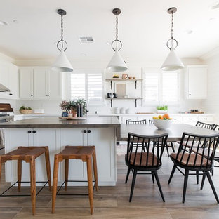 Beach style kitchen designs - Kitchen - beach style l-shaped brown floor kitchen idea in Sacramento with shaker cabinets, white cabinets, white backsplash and stainless steel appliances