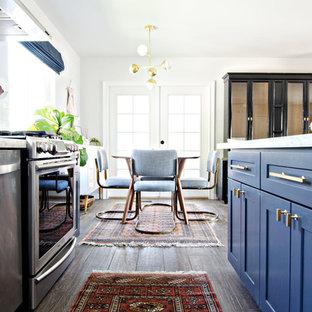 サンフランシスコの中くらいのミッドセンチュリースタイルのおしゃれなキッチン (エプロンフロントシンク、シェーカースタイル扉のキャビネット、青いキャビネット、白いキッチンパネル、セラミックタイルのキッチンパネル、シルバーの調理設備、濃色無垢フローリング、大理石カウンター) の写真