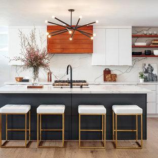 Inredning av ett modernt stort vit linjärt vitt kök, med en undermonterad diskho, släta luckor, vita skåp, marmorbänkskiva, vitt stänkskydd, stänkskydd i marmor, rostfria vitvaror, ljust trägolv, en köksö och beiget golv
