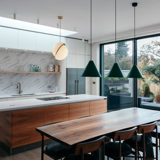 This is an example of a medium sized modern galley kitchen/diner in Gloucestershire with flat-panel cabinets, yellow cabinets, white splashback, marble splashback, an island, brown floors, a double-bowl sink, stainless steel appliances and light hardwood flooring.