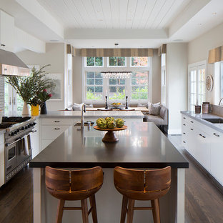 Example of a trendy dark wood floor eat-in kitchen design in San Francisco with an undermount sink, flat-panel cabinets, white cabinets, marble countertops, stainless steel appliances, an island and white backsplash
