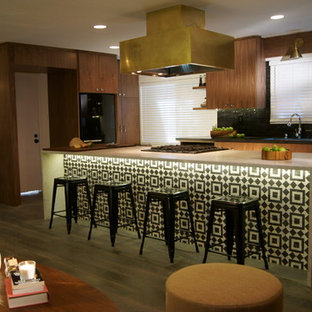 Photo of a mid-sized midcentury l-shaped open plan kitchen in Sacramento with an undermount sink, flat-panel cabinets, medium wood cabinets, quartz benchtops, black splashback, stone tile splashback, black appliances, medium hardwood floors, with island and brown floor.