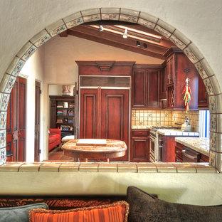 オレンジカウンティの巨大な地中海スタイルのおしゃれなアイランドキッチン (ダブルシンク、ヴィンテージ仕上げキャビネット、タイルカウンター、カラー調理設備、セラミックタイルの床) の写真