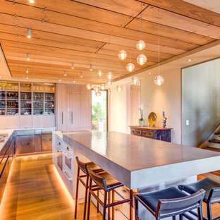 Contemporary kitchen ideas - Inspiration for a contemporary l-shaped medium tone wood floor and brown floor kitchen remodel in San Francisco with flat-panel cabinets, medium tone wood cabinets, concrete countertops, beige backsplash, paneled appliances, an island and gray countertops