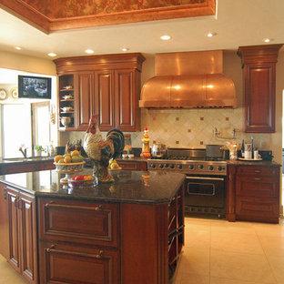 サンルイスオビスポの大きいヴィクトリアン調のおしゃれなキッチン (アンダーカウンターシンク、レイズドパネル扉のキャビネット、赤いキャビネット、御影石カウンター、ベージュキッチンパネル、石タイルのキッチンパネル、パネルと同色の調理設備、セラミックタイルの床) の写真