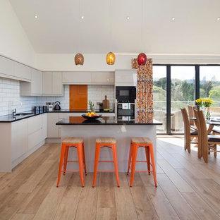 Идея дизайна: угловая кухня-гостиная среднего размера в современном стиле с плоскими фасадами, серыми фасадами, столешницей из оникса, оранжевым фартуком, фартуком из травертина, черной техникой, островом, черной столешницей, врезной раковиной, светлым паркетным полом и бежевым полом