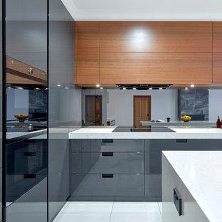アデレードの中サイズのモダンスタイルのおしゃれなキッチン (シングルシンク、フラットパネル扉のキャビネット、グレーのキャビネット、クオーツストーンカウンター、ガラス板のキッチンパネル、黒い調理設備、セラミックタイルの床、白い床) の写真