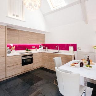 Foto di una cucina country con lavello sottopiano, ante lisce, ante in legno chiaro, paraspruzzi rosa, paraspruzzi con lastra di vetro, nessuna isola, pavimento nero e top bianco