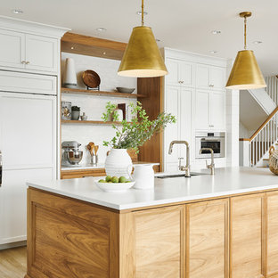 Design ideas for a large beach style l-shaped eat-in kitchen in Vancouver with a double-bowl sink, shaker cabinets, white cabinets, quartzite benchtops, white splashback, ceramic splashback, stainless steel appliances, vinyl floors, with island, beige floor and white benchtop.