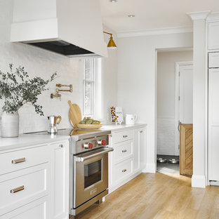 Large beach style l-shaped eat-in kitchen in Vancouver with a double-bowl sink, shaker cabinets, white cabinets, quartzite benchtops, white splashback, ceramic splashback, stainless steel appliances, vinyl floors, with island, beige floor and white benchtop.
