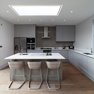 Photo of a medium sized contemporary l-shaped open plan kitchen in London with medium hardwood flooring, a submerged sink, flat-panel cabinets, grey cabinets, grey splashback, metro tiled splashback, stainless steel appliances and an island.