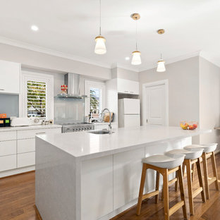 Photo of a mid-sized traditional galley open plan kitchen in Melbourne with flat-panel cabinets, white cabinets, medium hardwood floors, with island, brown floor, white benchtop, an undermount sink, blue splashback, glass sheet splashback and stainless steel appliances.
