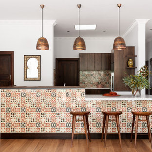 This is an example of a mediterranean u-shaped open plan kitchen in Melbourne with flat-panel cabinets, medium wood cabinets, multi-coloured splashback, stainless steel appliances, medium hardwood floors, with island, brown floor and white benchtop.