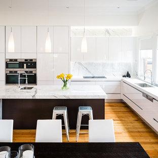 Geräumige Moderne Wohnküche in L-Form mit Unterbauwaschbecken, flächenbündigen Schrankfronten, weißen Schränken, Marmor-Arbeitsplatte, Kücheninsel, Küchenrückwand in Weiß, Küchengeräten aus Edelstahl, braunem Holzboden und Rückwand aus Marmor in Melbourne