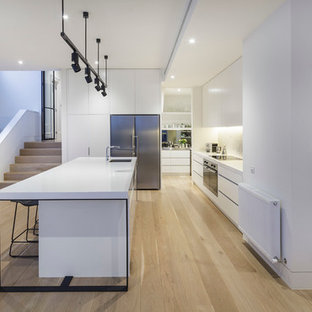 Inspiration for a large contemporary galley light wood floor kitchen remodel in Melbourne with an undermount sink, flat-panel cabinets, white cabinets, stone slab backsplash, stainless steel appliances and an island