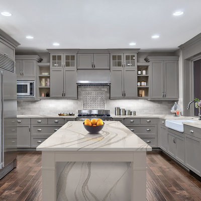 Inspiration for a transitional dark wood floor and brown floor kitchen remodel in Minneapolis with a farmhouse sink, shaker cabinets, gray cabinets, gray backsplash and an island