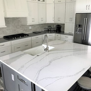 Large transitional l-shaped medium tone wood floor and brown floor eat-in kitchen photo in Other with an undermount sink, recessed-panel cabinets, white cabinets, quartz countertops, gray backsplash, stone tile backsplash, stainless steel appliances and an island