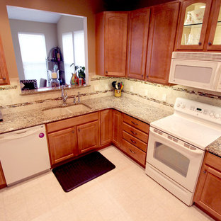 Example of a small classic l-shaped kitchen design in Cleveland with an undermount sink, raised-panel cabinets, medium tone wood cabinets, quartz countertops, beige backsplash, porcelain backsplash, white appliances and no island