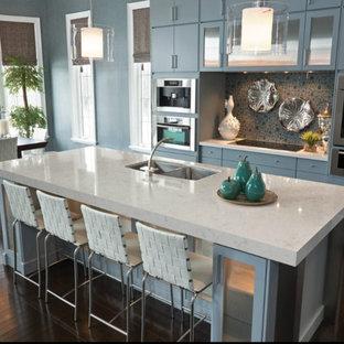 マイアミの中サイズのコンテンポラリースタイルのおしゃれなキッチン (ダブルシンク、フラットパネル扉のキャビネット、青いキャビネット、クオーツストーンカウンター、茶色いキッチンパネル、モザイクタイルのキッチンパネル、シルバーの調理設備、濃色無垢フローリング、茶色い床、白いキッチンカウンター) の写真