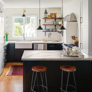 Farmhouse kitchen remodeling - Example of a farmhouse u-shaped medium tone wood floor and brown floor kitchen design in Portland with a farmhouse sink, shaker cabinets, black cabinets, white backsplash, stainless steel appliances, a peninsula and white countertops