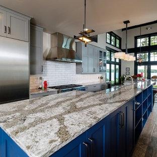 他の地域の大きいシャビーシック調のおしゃれなキッチン (アンダーカウンターシンク、落し込みパネル扉のキャビネット、青いキャビネット、クオーツストーンカウンター、白いキッチンパネル、サブウェイタイルのキッチンパネル、シルバーの調理設備の、セラミックタイルの床、マルチカラーの床) の写真