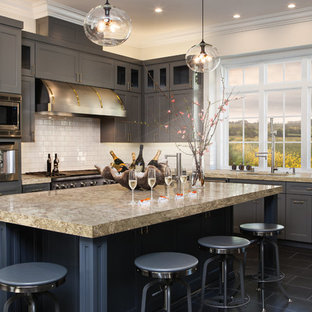 Example of a transitional l-shaped black floor kitchen design in Minneapolis with recessed-panel cabinets, gray cabinets, white backsplash, subway tile backsplash, stainless steel appliances and an island