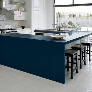 Inspiration for a large contemporary u-shaped eat-in kitchen in New York with flat-panel cabinets, white cabinets, quartz benchtops, white splashback, subway tile splashback, stainless steel appliances, ceramic floors, with island, a double-bowl sink, white floor and blue benchtop.