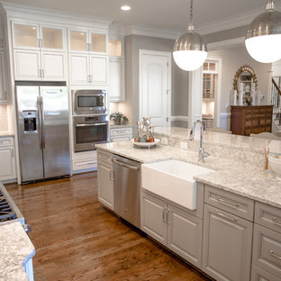 Example of a transitional l-shaped medium tone wood floor open concept kitchen design in Raleigh with a farmhouse sink, raised-panel cabinets, white cabinets, quartzite countertops, white backsplash, ceramic backsplash, stainless steel appliances and an island