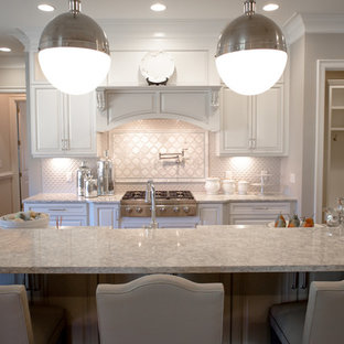 Inspiration for a transitional l-shaped medium tone wood floor open concept kitchen remodel in Raleigh with a farmhouse sink, raised-panel cabinets, white cabinets, quartzite countertops, white backsplash, ceramic backsplash, stainless steel appliances and an island