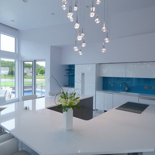 This is an example of an expansive contemporary u-shaped eat-in kitchen in Other with an undermount sink, flat-panel cabinets, grey cabinets, quartz benchtops, blue splashback, glass tile splashback, stainless steel appliances, marble floors and with island.