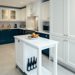 Inspiration for a mid-sized transitional u-shaped eat-in kitchen in Cambridgeshire with a drop-in sink, shaker cabinets, blue cabinets, granite benchtops, white splashback, glass sheet splashback, stainless steel appliances, slate floors, with island and beige floor.