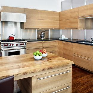 ボストンのコンテンポラリースタイルのおしゃれなキッチン (木材カウンター、シルバーの調理設備、ダブルシンク、フラットパネル扉のキャビネット、淡色木目調キャビネット、メタルタイルのキッチンパネル、メタリックのキッチンパネル) の写真
