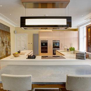 ケンブリッジシャーの大きいコンテンポラリースタイルのおしゃれなキッチン (ドロップインシンク、フラットパネル扉のキャビネット、珪岩カウンター、ベージュキッチンパネル、パネルと同色の調理設備、磁器タイルの床) の写真