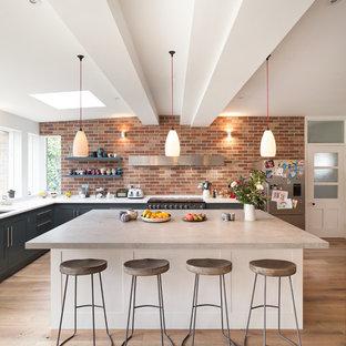 Bild på ett stort vintage vit vitt kök, med luckor med infälld panel, grå skåp, bänkskiva i koppar, integrerade vitvaror, en köksö, en undermonterad diskho, rött stänkskydd, stänkskydd i tegel, mellanmörkt trägolv och brunt golv