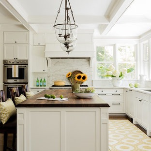 Inspiration for a traditional kitchen in Boston with a submerged sink, shaker cabinets, white cabinets, white splashback, marble splashback, integrated appliances, dark hardwood flooring, an island, brown floors and wood worktops.