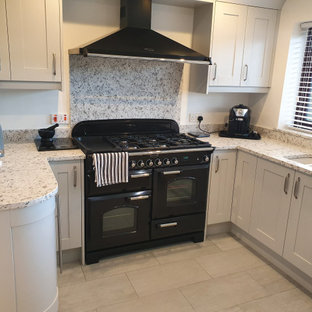 ウエストミッドランズの中サイズのモダンスタイルのおしゃれなキッチン (一体型シンク、シェーカースタイル扉のキャビネット、グレーのキャビネット、珪岩カウンター、マルチカラーのキッチンパネル、黒い調理設備、セラミックタイルの床、アイランドなし、グレーの床、マルチカラーのキッチンカウンター) の写真