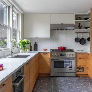 Retro Küche ohne Insel in U-Form mit Unterbauwaschbecken, flächenbündigen Schrankfronten, hellen Holzschränken, Quarzwerkstein-Arbeitsplatte, Küchenrückwand in Weiß, Rückwand aus Marmor, Küchengeräten aus Edelstahl, Porzellan-Bodenfliesen, grauem Boden und weißer Arbeitsplatte in Boston