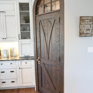 Exempel på ett stort rustikt svart svart kök, med en undermonterad diskho, luckor med infälld panel, vita skåp, beige stänkskydd, stänkskydd i glaskakel, rostfria vitvaror, mörkt trägolv, en köksö, brunt golv och bänkskiva i onyx