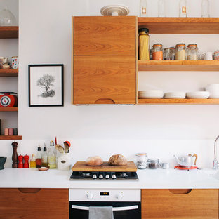 Inspiration for a medium sized retro single-wall kitchen in London with a double-bowl sink, flat-panel cabinets, white cabinets, quartz worktops, white appliances and white worktops.