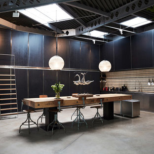 This is an example of an expansive industrial single-wall kitchen/diner in London with flat-panel cabinets, black cabinets, stainless steel appliances, concrete flooring, grey floors, a built-in sink, stainless steel worktops and brown splashback.