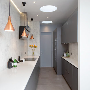 Medium sized contemporary galley enclosed kitchen in London with a double-bowl sink, flat-panel cabinets, grey cabinets, white splashback, marble splashback, no island, grey floors, white worktops and integrated appliances.