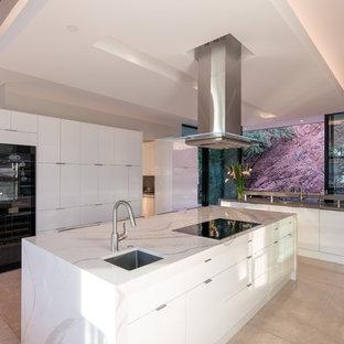 Foto di una cucina contemporanea con lavello sottopiano, ante lisce, ante bianche, top in quarzite, elettrodomestici in acciaio inossidabile, pavimento in travertino, isola, pavimento beige e top bianco