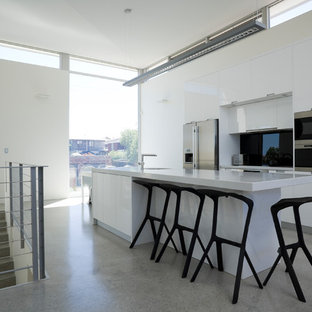 Photo of a contemporary galley kitchen in Perth with flat-panel cabinets, white cabinets, black splashback, glass sheet splashback, stainless steel appliances, terrazzo floors, with island and grey floor.