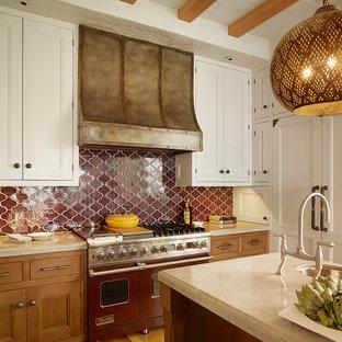 サンフランシスコの大きい地中海スタイルのおしゃれなキッチン (エプロンフロントシンク、インセット扉のキャビネット、白いキャビネット、ライムストーンカウンター、ベージュキッチンパネル、ライムストーンの床、パネルと同色の調理設備、無垢フローリング) の写真