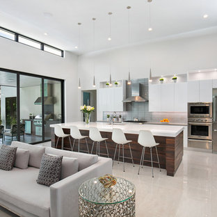 Inspiration for a large modern l-shaped open plan kitchen in Tampa with an undermount sink, flat-panel cabinets, white cabinets, quartz benchtops, grey splashback, glass tile splashback, stainless steel appliances, porcelain floors, with island, white floor and grey benchtop.