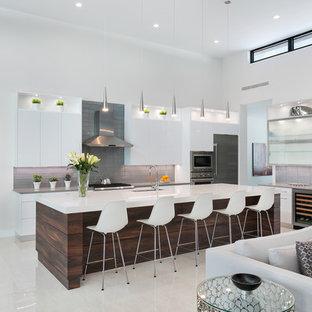 タンパの大きいモダンスタイルのおしゃれなキッチン (アンダーカウンターシンク、フラットパネル扉のキャビネット、白いキャビネット、クオーツストーンカウンター、グレーのキッチンパネル、ガラスタイルのキッチンパネル、シルバーの調理設備の、磁器タイルの床、白い床、グレーのキッチンカウンター) の写真