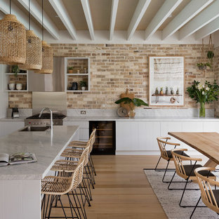 Inspiration for a beach style l-shaped eat-in kitchen in Sydney with a drop-in sink, flat-panel cabinets, white cabinets, brick splashback, stainless steel appliances, light hardwood floors and with island.