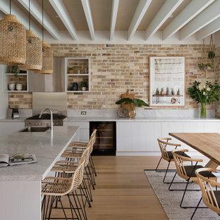シドニーのビーチスタイルのおしゃれなキッチン (ドロップインシンク、フラットパネル扉のキャビネット、白いキャビネット、レンガのキッチンパネル、シルバーの調理設備の、淡色無垢フローリング) の写真