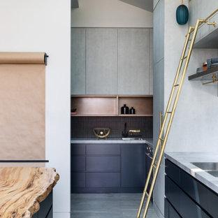 Modelo de cocina industrial con encimera de mármol, salpicadero verde, salpicadero de mármol, suelo de cemento, una isla, suelo gris y encimeras multicolor